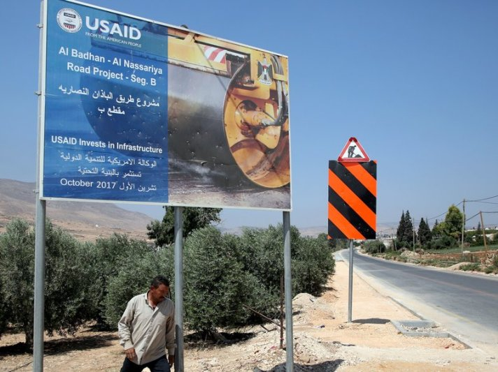 A Palestinian man walks near a USAID billboard in the West Bank village of Badhan, north of Nablus, last August. Since January, U.S. financing for humanitarian programs serving Palestinians has been suspended [Jaafar Ashtiyeh/AFP/Getty Images]