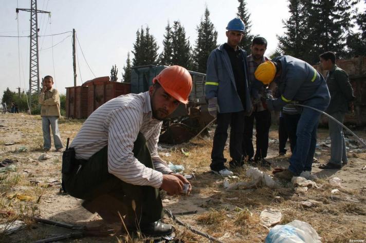 Palestinian workers can be seen repairing the damaged power lines in Gaza City [Credit: Apa images]
