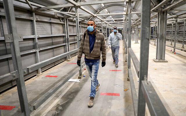 Palestinian workers walk through Meitar checkpoint